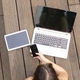搜寻在多个设备屏幕的女孩工作 免版税库存照片
