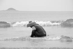 搜寻在海滩的亚裔妇女蛤蜊 免版税库存照片