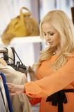 搜寻在衣裳中的美丽的妇女在商店 库存图片