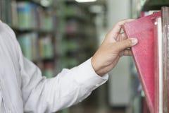 搜寻在走道的人书在图书馆里 库存图片