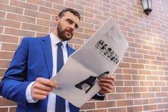 搜寻某事在报纸的商人 库存照片