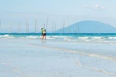 搜寻从海滩的人小壳 免版税库存图片