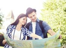 搜寻他们的与地图的下个目的地的旅行的夫妇 免版税库存照片