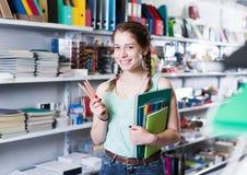 搜寻铅笔和标志的女小学生在书店 库存图片