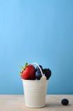 搪瓷桶充满在木头的新鲜水果莓果与蓝色 库存照片