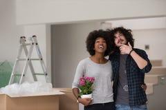 搬入一个新的家的不同种族的夫妇 库存图片