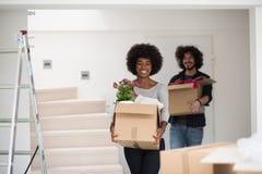 搬入一个新的家的不同种族的夫妇 免版税库存照片
