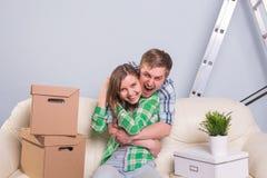搬入他们新的家的年轻快乐的夫妇 免版税图库摄影