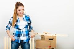 搬入公寓汇编家具的妇女 免版税库存图片