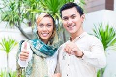 搬入房子的亚洲回教夫妇 免版税库存照片