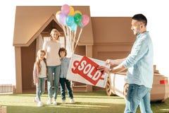 搬入新的cardbord房子的愉快的年轻家庭 免版税库存图片