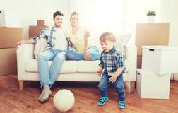 搬到新的家和打球的愉快的家庭 免版税库存图片