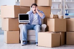 搬到有箱子的新房的年轻人 免版税库存图片