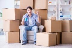 搬到有箱子的新房的年轻人 库存照片