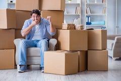 搬到有箱子的新房的年轻人 免版税库存照片
