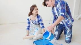 搬到的概念一个新的家 年轻夫妇在他们新的家更新并且绘墙壁 股票视频