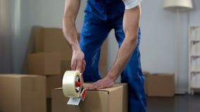 搬家公司工作者包装纸板箱,质量送货业务 库存照片