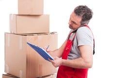 搬家工人与剪贴板和电话的人多任务 库存照片