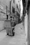 搬运工在有交付包裹的威尼斯在推车 库存图片