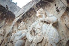 搬运工` s雕象岩石雕刻在龙门石窟的,洛阳,河南 免版税库存图片