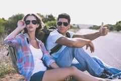 搭车在乡下路的夫妇 免版税库存图片