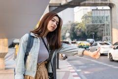 搭车在路的可爱的年轻亚裔旅行女孩在城市 生活是旅途概念 图库摄影