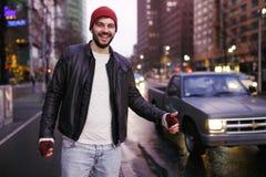 搭车在路的英俊的年轻游人 在高速公路的捕捉汽车 旅游业和人概念 E 免版税库存照片