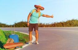 搭车沿一条农村山路的英俊的年轻人-有行李的远足者人和longboard设法停止汽车 免版税库存照片