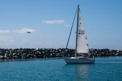 搭载蓝绿色水的帆船四位乘客与直升机接近 免版税图库摄影