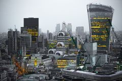 携带无线电话大厦和金丝雀码头银行业务和办公室唱腔在背景 伦敦英国 免版税库存照片