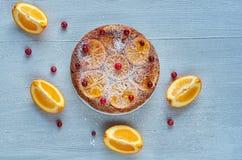 搽粉的柑橘饼用焦糖的桔子和新鲜的红色莓果在灰色桌上 用未加工的橙色切片装饰的橙色饼 图库摄影