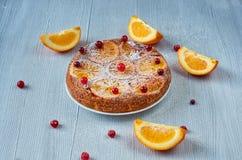 搽粉的柑橘饼用焦糖的桔子和新鲜的红色莓果灰色表面上 与未加工的橙色切片的甜橙饼 库存图片