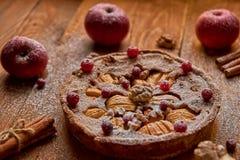 搽粉的苹果饼用新鲜的蔓越桔和核桃装饰用苹果,桂香 立即可食被烘烤的搽粉的苹果饼 免版税库存图片