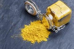 搽粉调味料在一块黑石头的香料姜黄 免版税库存照片