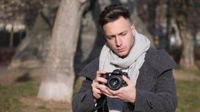 摄制录影镜头的英俊的年轻男性摄影师外面 影视素材