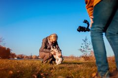 摄制有狗的Videographer妇女在秋天公园 使用steadicam和照相机的人做英尺长度 录影射击 库存图片
