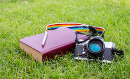 摄制照相机、书和笔在草皮地面 免版税库存照片