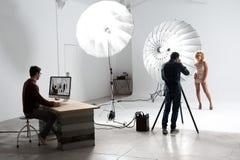摄影师与一个逗人喜爱的模型一起使用在一个专业演播室 图库摄影