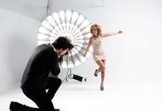 摄影师与一个逗人喜爱的模型一起使用在一个专业演播室 免版税图库摄影