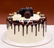 摄影师与一台照片照相机的生日蛋糕在上面 免版税库存图片