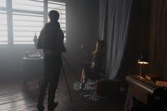 摄影师与模型一起使用在演播室,葡萄酒 免版税库存照片
