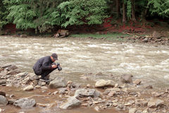 摄影师为粗砺的河照相 库存图片