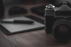 摄影师书桌静物画在家庭办公室内部的 专业照片媒介运转的设备,照相机机身,透镜,显示器 免版税库存照片