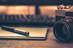 摄影师书桌静物画在家庭办公室内部的 专业照片媒介运转的设备,照相机机身,透镜,显示器 免版税图库摄影