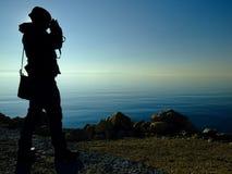 摄影师人剪影拍在湖边的一张照片在日落 免版税库存照片