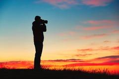 年轻摄影师剪影享用太阳 日出的摄影师 库存照片
