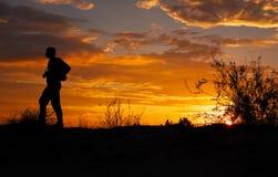 摄影师剪影有他的照相机的在日落 免版税图库摄影