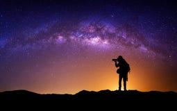 摄影师剪影有照相机和银河的 库存照片