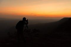 摄影师剪影,当他拍摄在山的照片 免版税库存照片