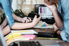 年轻摄影师和图表设计师在工作在演播室办公室 免版税库存图片